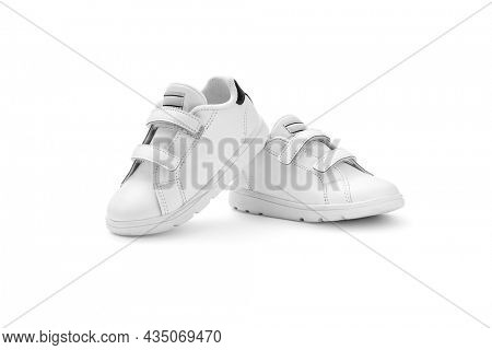 Kid white sneakers with velcro fasteners on white background, including clipping path