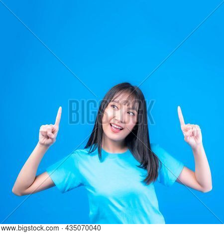 Beautiful Asian Woman Cute Girl With Bangs Hair Style In Blue T Shirt Smiling And Pointing Finger To
