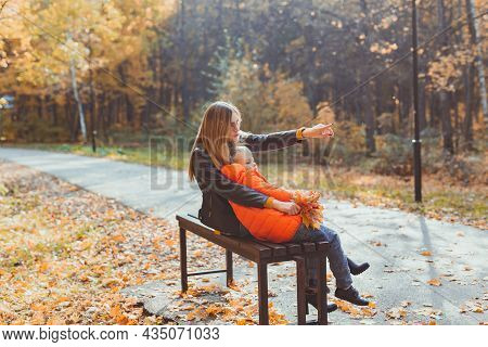 Single Parent Mother And Child Boy In The Autumn In Park Sit On Bench. Fall Season And Family Concep