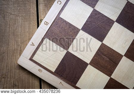 Wooden Chess Board On A Wooden Table. Board Game, Top View