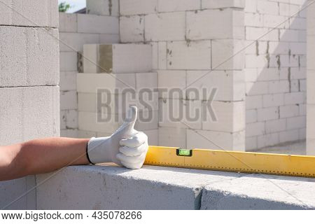 Construction Level And Hands Of The Builder At The Construction Site