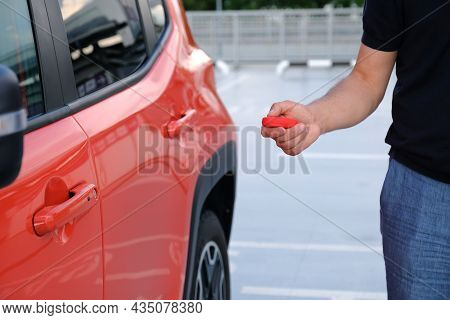 Man Hand Pushing Button On Remote Control Car Key.