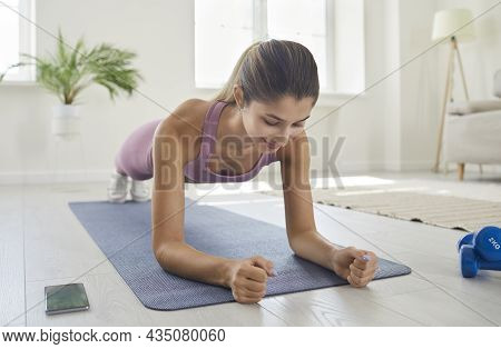 Fit Young Woman Doing A Forearm Plank Exercise During Her Fitness Workout At Home