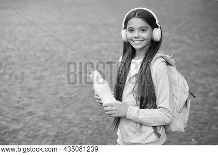 Cheerful Teen Girl In Headset With Favorite Song Feel Thirsty After Fitness. And Hold Water Bottle,