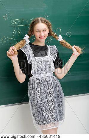 Happy Teenage Girl In Uniform Holding Long Braids. Attractive Student Girl Wearing Retro Soviet Scho
