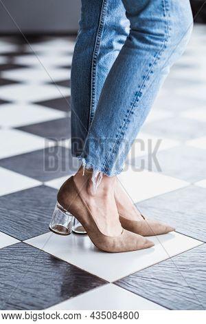 Beautiful Slim And Slender Female Legs In Jeans In Beige High Heels. Womans Legs On A Checkerboard F