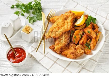 Breaded Chicken Cutlets With Oven Roasted Potato Wedges On A White Plate With Golden Cutlery On A Wh