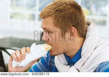 A Hungry Young Man Is Eating A Big Appetizing Hot Dog With Sausage In A Cafe. An Unshaven Man Eats I