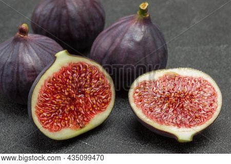 Two Halves Of  Fig. Three Whole Figs. Black Background. Top View