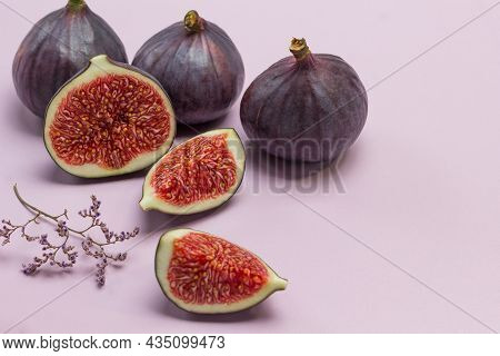 Half Fig And A Wedge Of Fig. Three Whole Figs. Pink Background. Top View