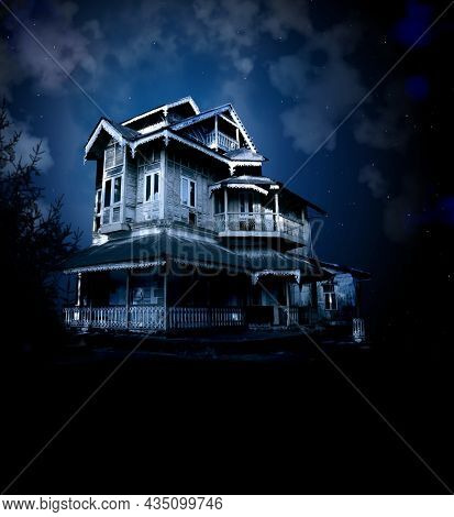 Haunted house on night sky background. Old abandoned house and mysterious landscape. Photo toned in blue color. Copy space for text