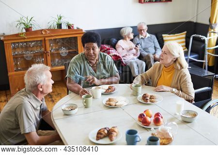 High Angle View Of Diverse Group Of Senior People Enjoying Breakfast In Cozy Nursing Home, Copy Spac