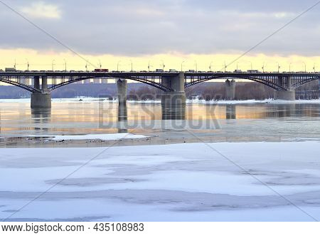The Bank Of The River Ob In Novosibirsk. Oktyabrsky Automobile Bridge On A Winter Evening, The First