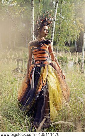 Amazing brunette beauty posing in autumn scenery