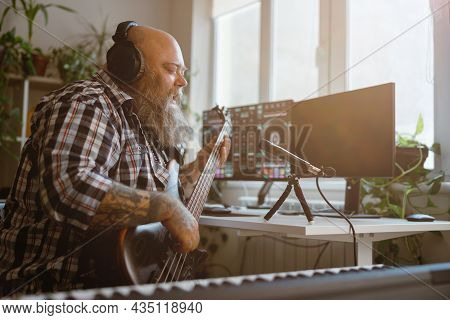 Mature Composer Plays Bas Guitar Recording Track At Workplace In Home Studio