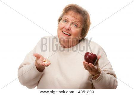 Confused Senior Woman Holding Apple And Vitamins