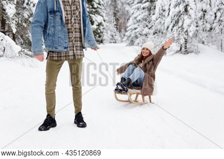 Young Man Pulling Sledge With His Joyful Girlfriend On Winter Day In Forest