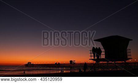 Young Teen Girls Silhouettes Near Lifeguard Tower, Friends On Pacific Ocean Beach, Sunset Dusk In Oc