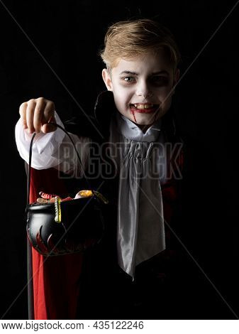 Boy with cauldron basket and worm sweets dressed as vampire for Halloween party going trick or treating. Studio portrait isolated over black background