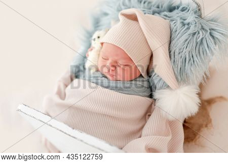 Newborn baby boy wearing knitted hat sleeping on white small designed bed. under blanket Adorable infant child napping during studio photoshoot