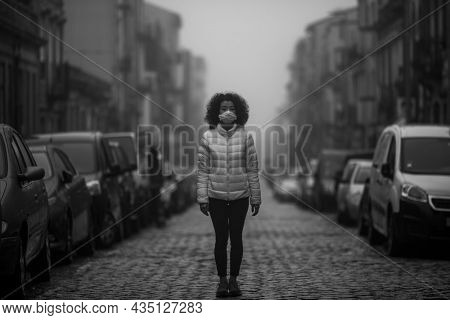 An asian woman in the antiviral mask stands in the street in cloudy weather. Black and white photo.