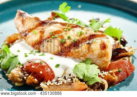 Healthy food - baked salmon steak with tomato salad and white sauce. Roast salmon with vegetables on contemporary plate in asian style. Restaurant dish - salmon filet with hard shadow
