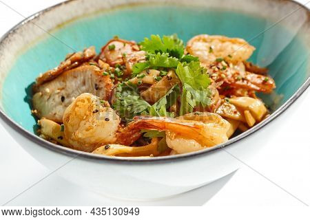 Pan asian food - udon with prawn, chicken wok on white background. Noodle with chicken and prawn in ceramic bowl. Indonesian wok with udon noodles. Spicy thai dish from noodle with shrimp and chicken