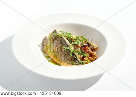 Roast white fish with vegetables isolated on white background. Grill halibut with crispy skin and tomato salad. Fish fillet with vegetables garnish in minimal style. Seafood Restaurant menu