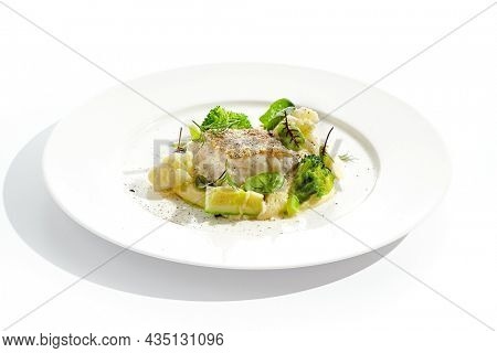 Roasted cod with mashed potatoes and broccoli. White fish fillet with skin with vegetables isolated on white background. Healthy food in restaurant menu. Fish and cabbages in minimalism style