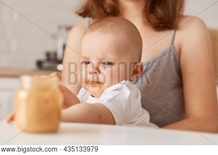 Portrait Of Cute Curious Baby And Unknown Woman Holding Feeds Infant Child With Puree, People Posing