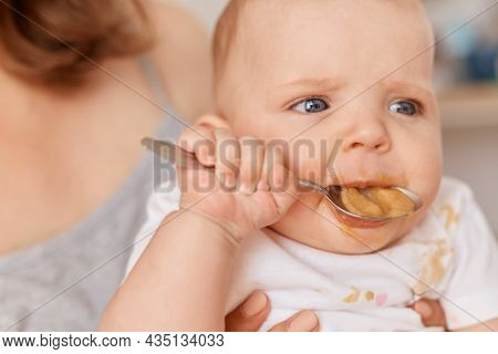 Close Up Portrait Of Cute Toddler Girl Trying To Eat Fruit Or Vegetable Puree With Spoon, Unknown Wo
