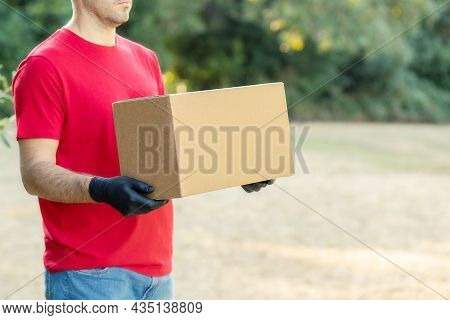 Delivery Man Holding Cardboard Boxes On The Farm In Medical Gloves. Online Shopping And Express Deli