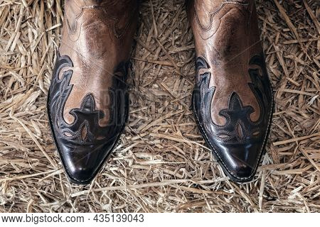 Cowboy boots standing on hay in barn from above