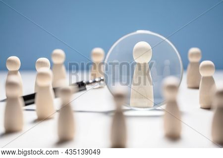 Recruitment and job search magnifying glass with wooden people concept for human resources and choosing the right people