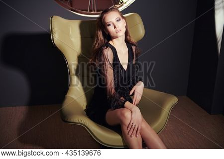 Portrait of a stunning fashionable woman in a black evening dress posing in a luxurious leather armchair. Modern interior, furniture.
