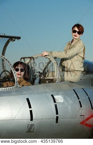 Professional commercial pilots women wearing uniform and sunglasses pose sitting in their aircraft cockpit before taking off. Women in aviation.