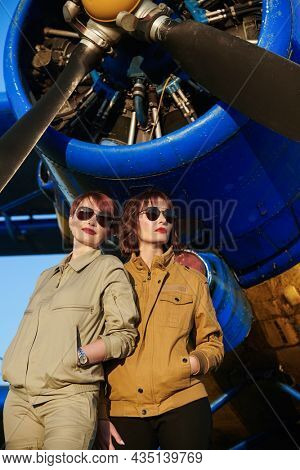 Aviation. Two professional female commercial aviation pilots in uniform and sunglasses stand in front of their plane on the airfield looking into the distance.