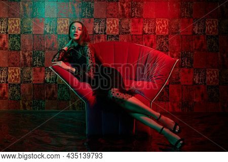 Beautiful young woman in black evening dress sits on the armchair in luxury apartment with red lighting. Glamorous lifestyle. Beauty, fashion. Modern interior, furniture.
