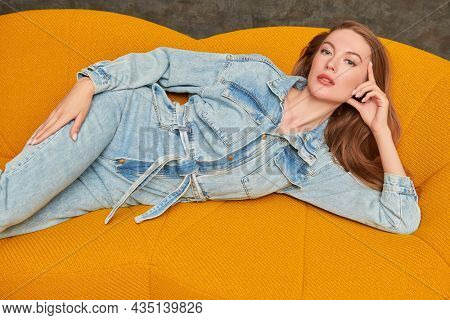 Fashion shot. Beautiful fashion model girl poses in denim overalls on a bright yellow sofa in a modern apartment. Modern interior and furniture.