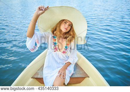 Summer vacation. Beautiful stylish blonde girl in a light white dress and a wide-brimmed straw hat posing on a sea trip. Summer fashion and activities.