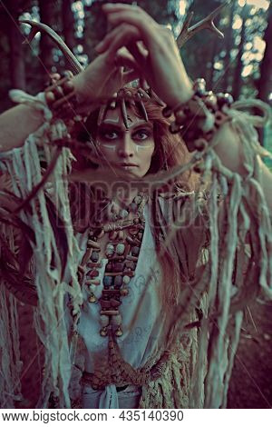 A mystical woman shaman in ethnic dress and deer antlers headdress performs a ritual dance in the forest. Fairy forest witch. Fantasy. Halloween.