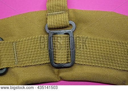 One Black Plastic Carabiner With A Green Fabric Harness On The Backpack In The Pink Background