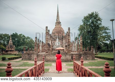 The Scenery Of A Woman With Her Lanna-style Umbrella Standing In Front Of Wat Mahathat Temple On A C