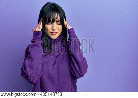 Young brunette woman with bangs wearing turtleneck sweater with hand on head for pain in head because stress. suffering migraine.