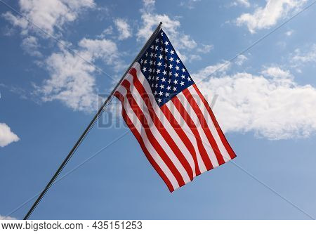 Us National Flag Hanging On Flagstaff Over Cloudy Blue Sky, Symbol Of American Patriotism, Low Angle