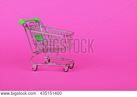 Close Up Empty Toy Metal Supermarket Shopping Cart Over Vivid Pink Background With Copy Space, Low A