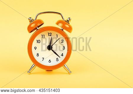 Close Up One Small Orange Metal Twin Bell Retro Alarm Clock Over Pastel Yellow Paper Background With