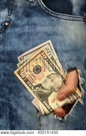 Hand Holds Several Different Value Us Dollar Paper Currency Banknotes In Jeans Rip Hole, Low Angle V