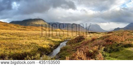 Low cloud in the Scottish highlands. Panoramic view with a stream running through the mountains in autumn. Scotland, UK