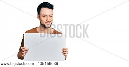 Hispanic man with beard holding blank empty banner winking looking at the camera with sexy expression, cheerful and happy face.